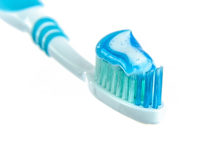 white and blue toothbrush with white and blue toothpaste