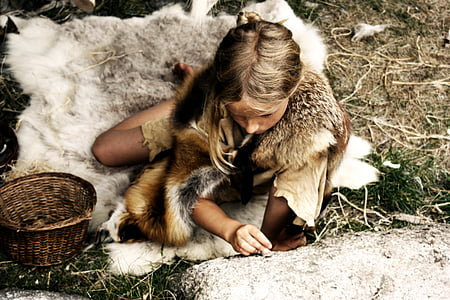woman wearing animal hide sitting on grass