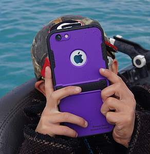 man holds silver iPhone 7 with purple case