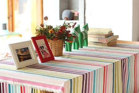 two photo frames beside flower arrangement on table