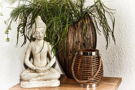 gautama Buddha figurine near brown wooden vase