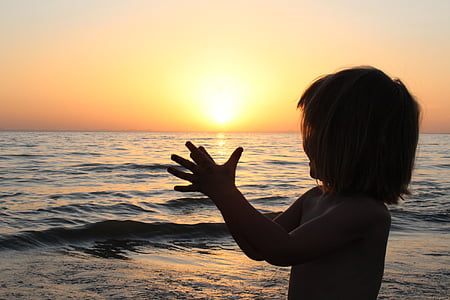silhouette photo of girl beside body of water