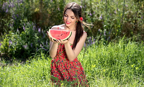 woman in red floral dress holding watermelon fruit