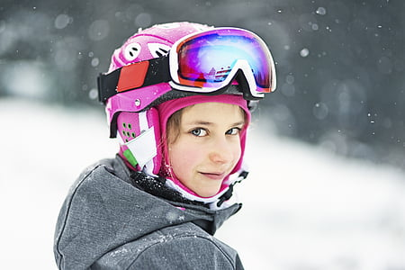 girl wearing pink helmet and snow goggles