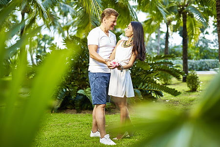 man and woman standing on green grass while holding hands during daytime