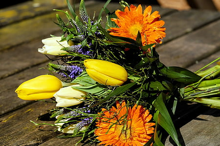 yellow and orange petaled flower bouquet on brown wooden surface