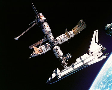 black and white space shuttle with docked spaceship