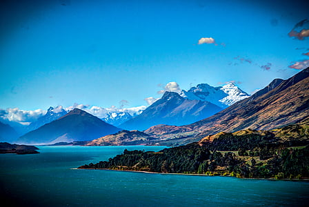 mountain range near water with clouds