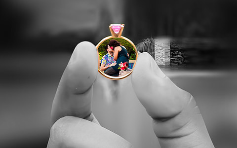 person holding gold-colored ring with pink gemstone encrust