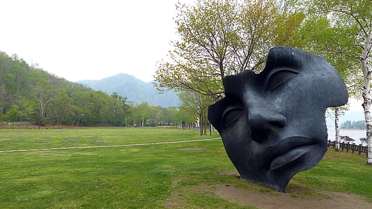face statue near body of water during daytime