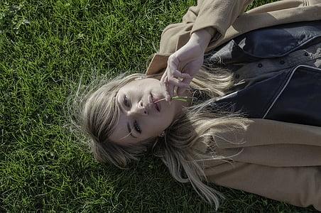 women's wearing brown coat lying on green grass field