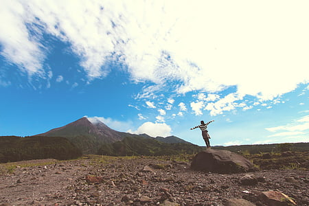 woman standing on rock formation near mountain under blue clouds during daytime