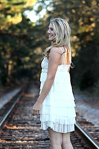 closeup photography of woman standing on train rail wearing white spaghetti strap dress