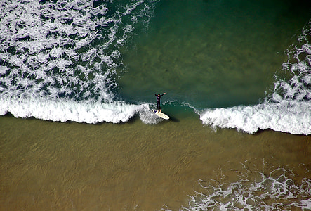 aerial photo of person surfing on beach during daytime
