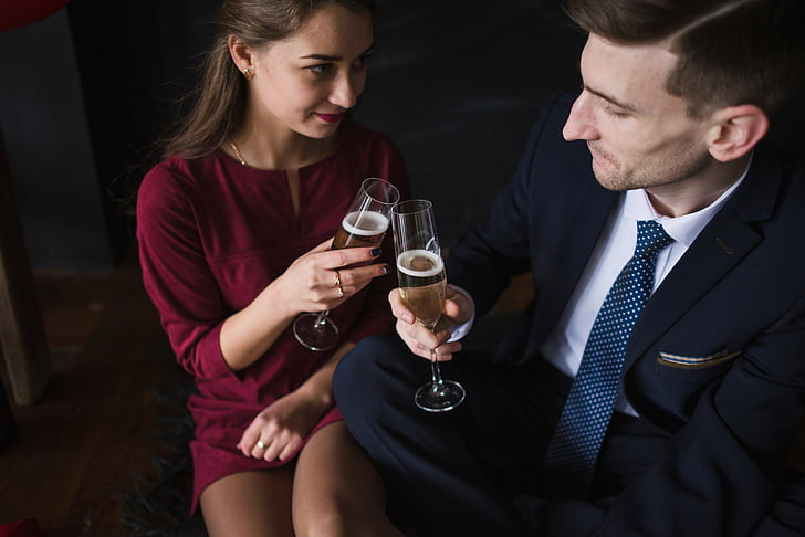 man and woman toasting champagne glass
