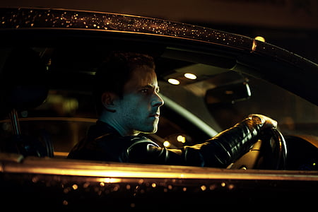 man wearing black jacket riding car