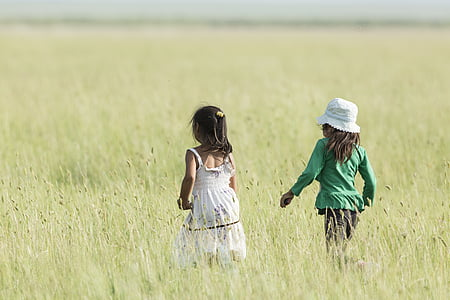 two girls walking on grass field during daytime