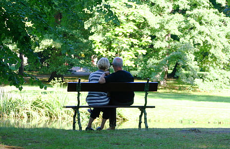 man and woman sitting on the bench surrounded with trees