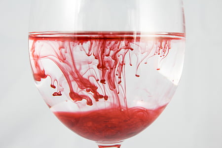 red liquid in clear drinking glass