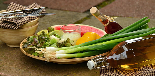 vegetables and fruits on brown plate near brown bowl and clear glass bottles