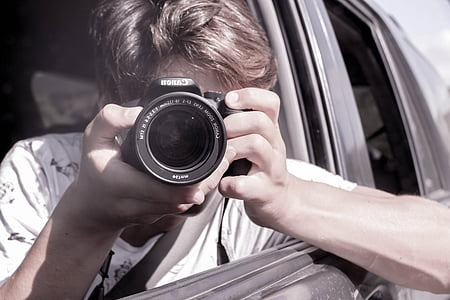 person holding DSLR camera inside car during daytime
