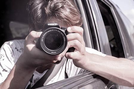 person holding DSLR camera inside car during daytime