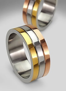 two gold-and-silver-colored rings on white panel