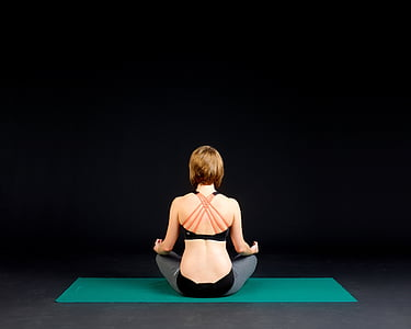 woman in black sports bra sitting on green yoga mat