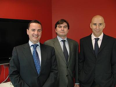 three men standing beside flat screen TV