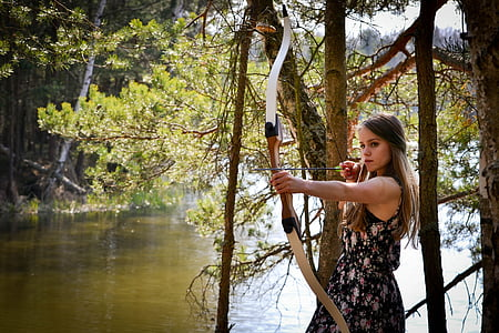 woman holding brown composite bow