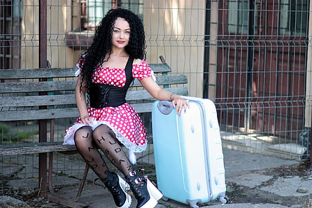woman sitting on bench wearing dress and holding travel luggage during daytime