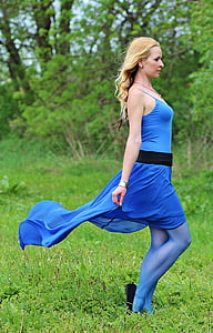 photograph of woman wearing blue spaghetti strap dress standing on grass field making side view posture