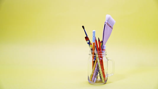 assorted-color pens and pencils in clear glass mason jar