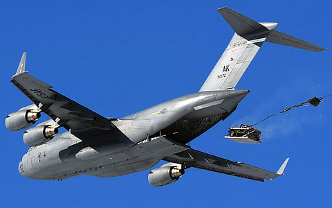 gray aircraft dropping truck