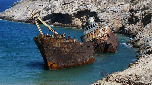 corroded shipwreck docked on body of water