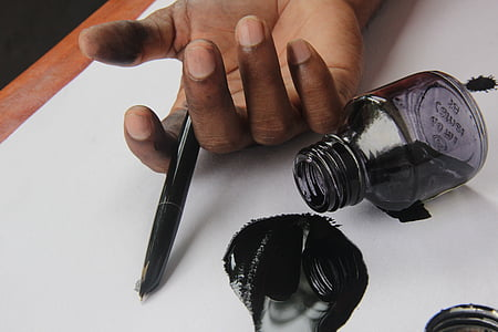 person holding fountain pen and ink