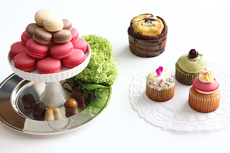 cupcakes on plate and stand above white surface