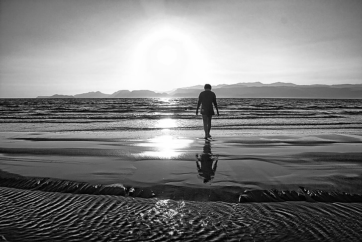 grayscale photo of person walking towards sea