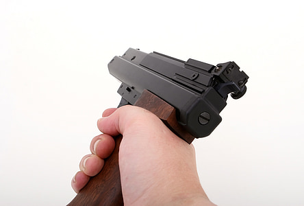 person's hand holding semi-automatic pistol