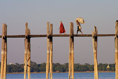 man in red robe standing on wooden bridge