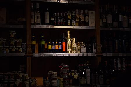 assorted beverage bottle on wooden rack