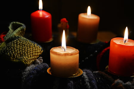 four red and beige pillar candles lighted up