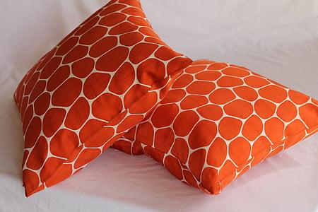 two orange-and-white throw pillows