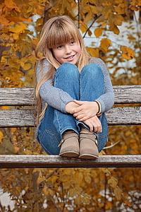 girl sitting on brown bench