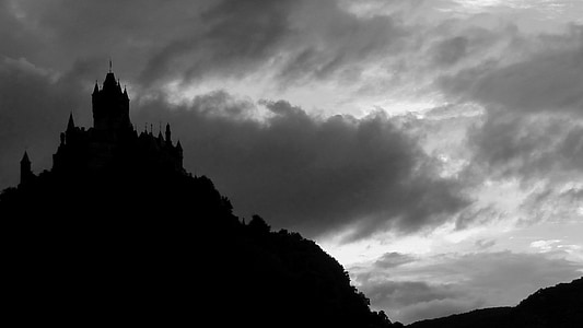 silhouette of castle on top of mountain under cloudy sky