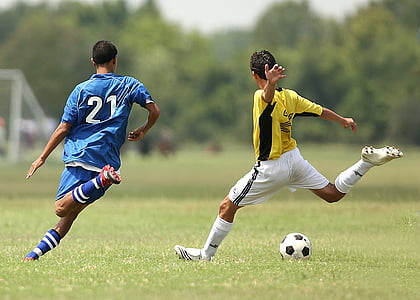 two man playing soccer during daytime