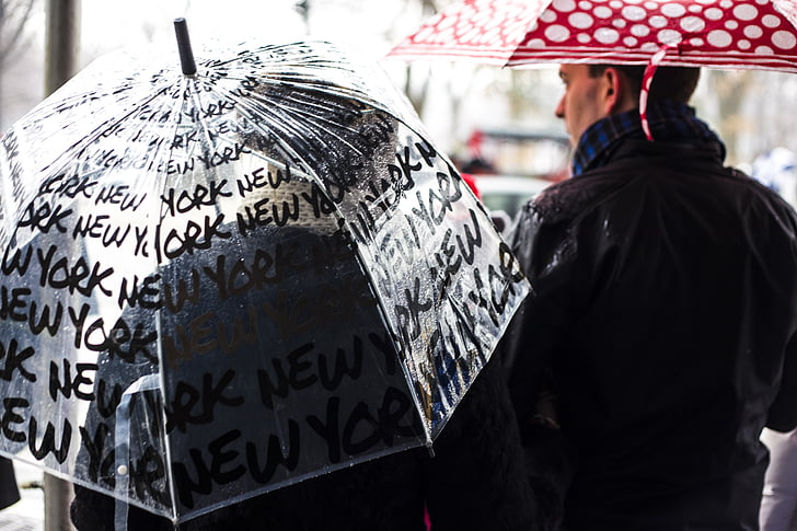 person holding clear umbrella near man wearing black jacket holding red umbrella at daytime