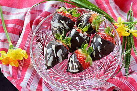 chocolate coated strawberries on clear cut glass bowl