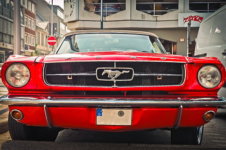 red Ford Mustang Fastback parked on gray road