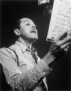 graysale photography of man singing while holding musical script
